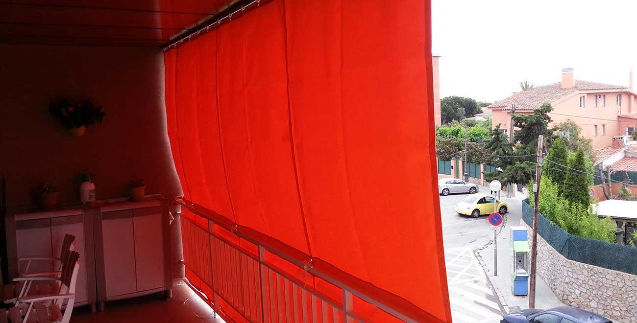 Balcón con toldo de cortina corredera roja - vista lateral